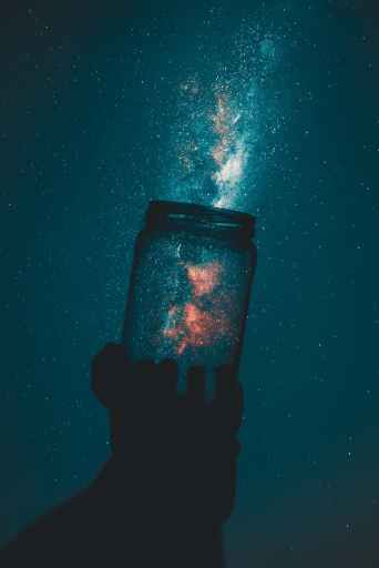 Glitter escaping from an open jar into the night sky.  Unleash your law of attraction affirmations on the universe, and you will have what you want in no time.