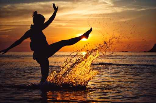 Spiritually free woman splashing in the ocean as sunset after reading this article full of deep let go quotes.