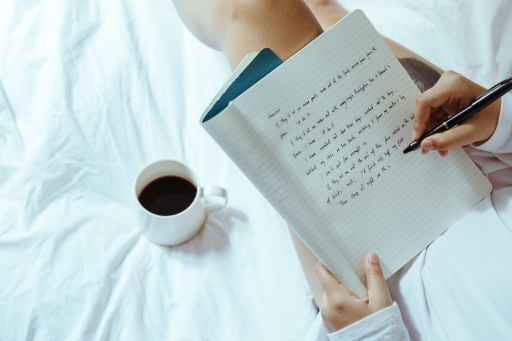 Woman with coffee writing in law of attraction affirmations in notebook on bed.