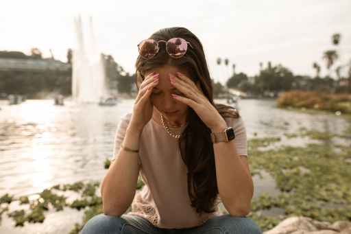 distressed woman sitting on lakeside and touching face in despair wondering why does life suck