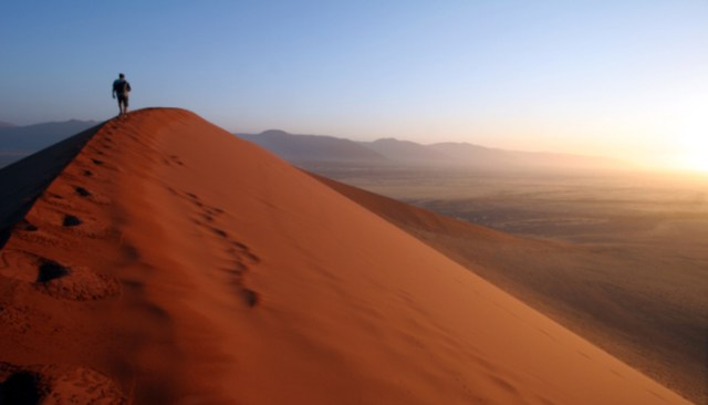Man approaching the summit of Dune 45, Sossusvlei, Namibia. Sunrise is visible on the right-hand side of the image. Other Africa images