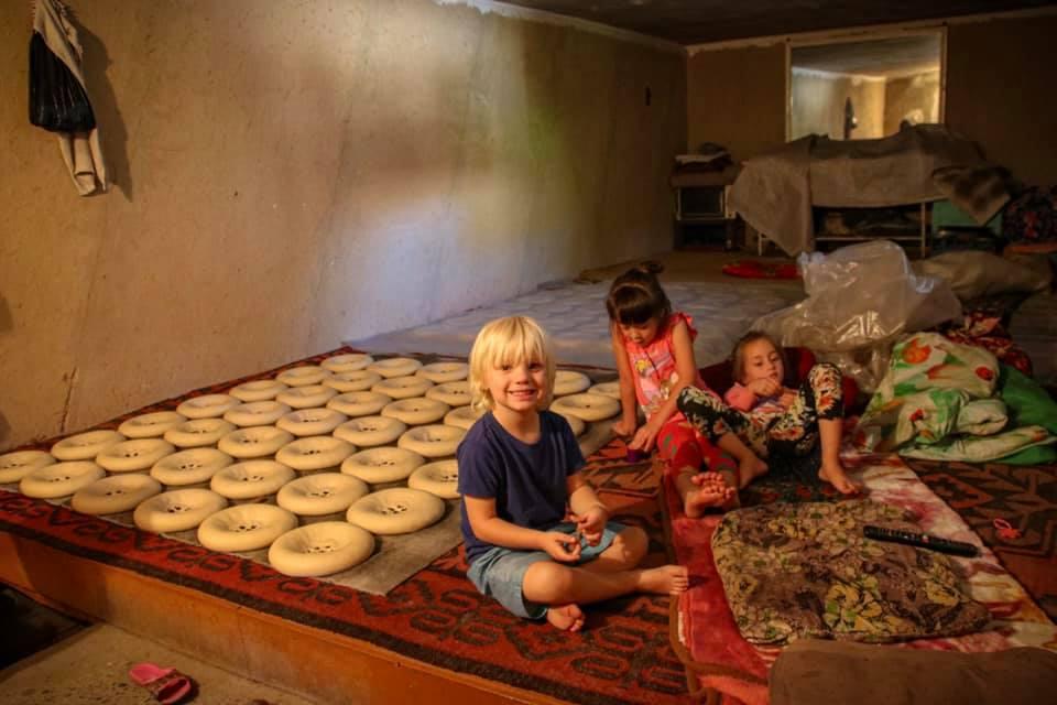 Oscar learning how to make Samarkand bread during our travel in Uzbekistan with kids. Uzbekistan travel blog.