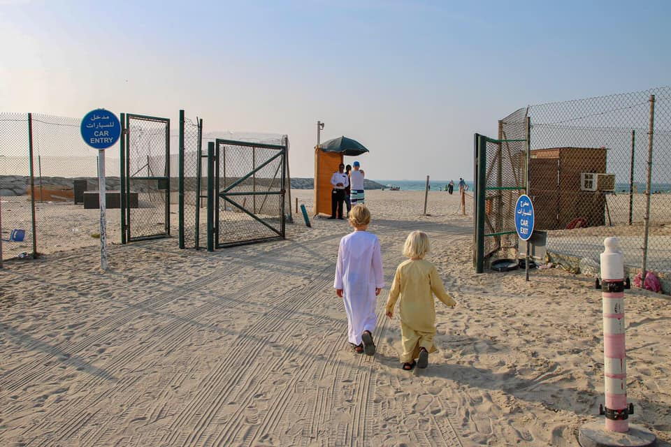 The boys walking on to the beach at Sharjah in their robes. Exploring the UAE with kids.
