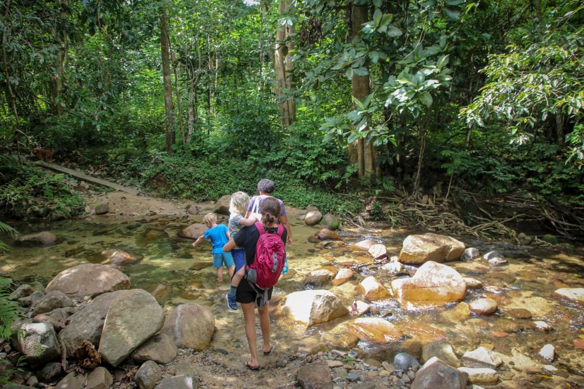 Carrying Oscar across the river on the way to Biasevu Waterfall. Hiking in Fiji with kids.