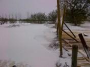 A damaged fence alongside substantial snow accumulation in MacGregor, MB.