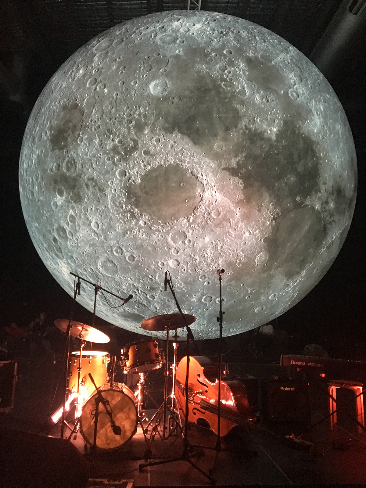 moon sculpture in light with band equipment in red light beneath