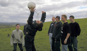 boys play football with wind turbines in the background