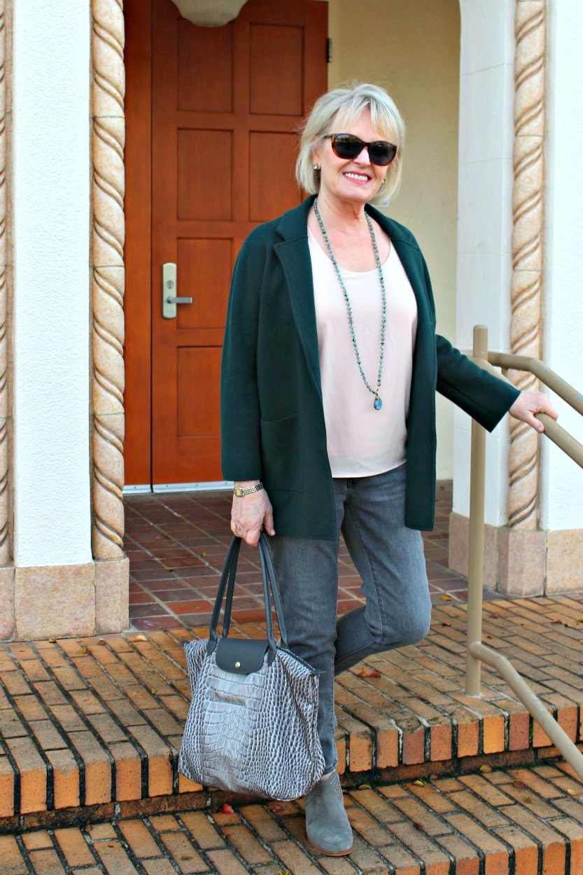 jennifer connolly of a well styled life wearing gray jeans, gray toe bag and green sweater jacket