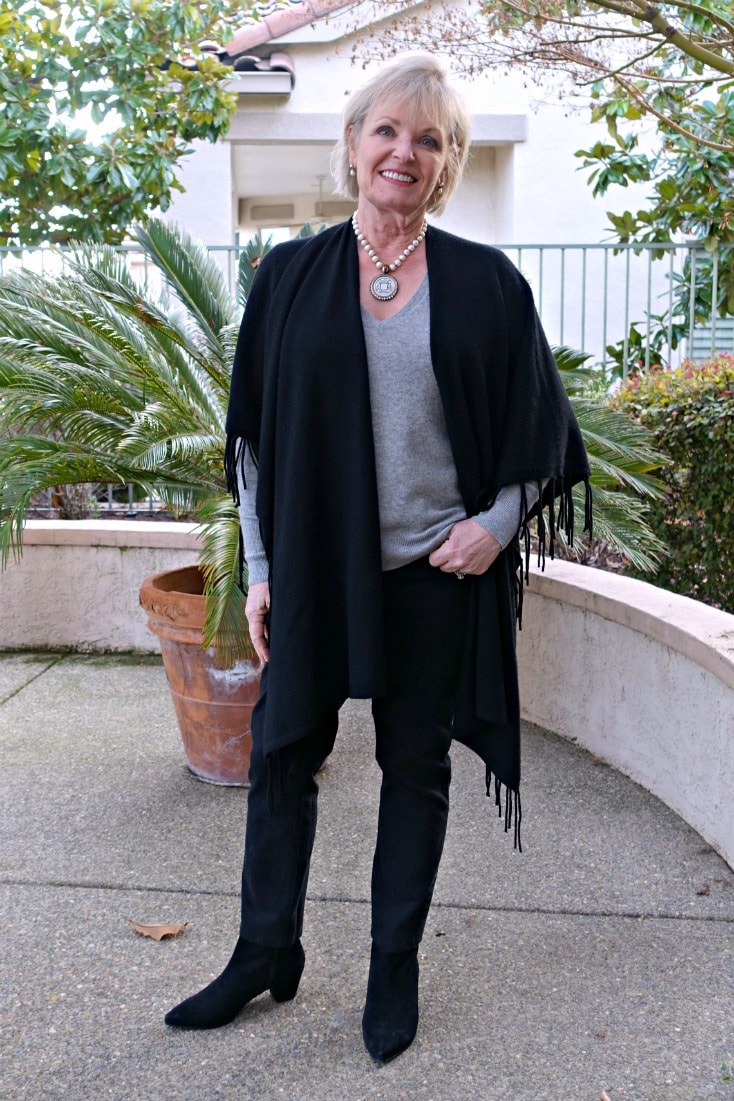 Jennifer Connolly wearing black ruana over gray sweater and black jeans