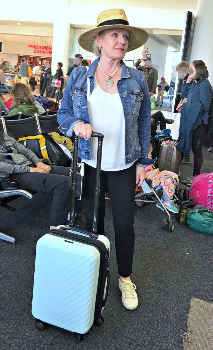 Jennifer Connolly of A Well Styled Life wearing straw hat, denim jacket and Eileen Fisher pants