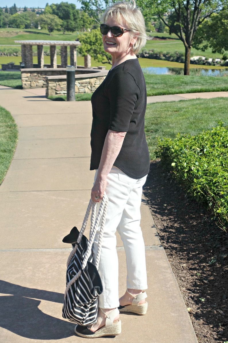 casual tee outfit of cream jeans, black tee, black espadrilles and striped tote on A Well Styled Life