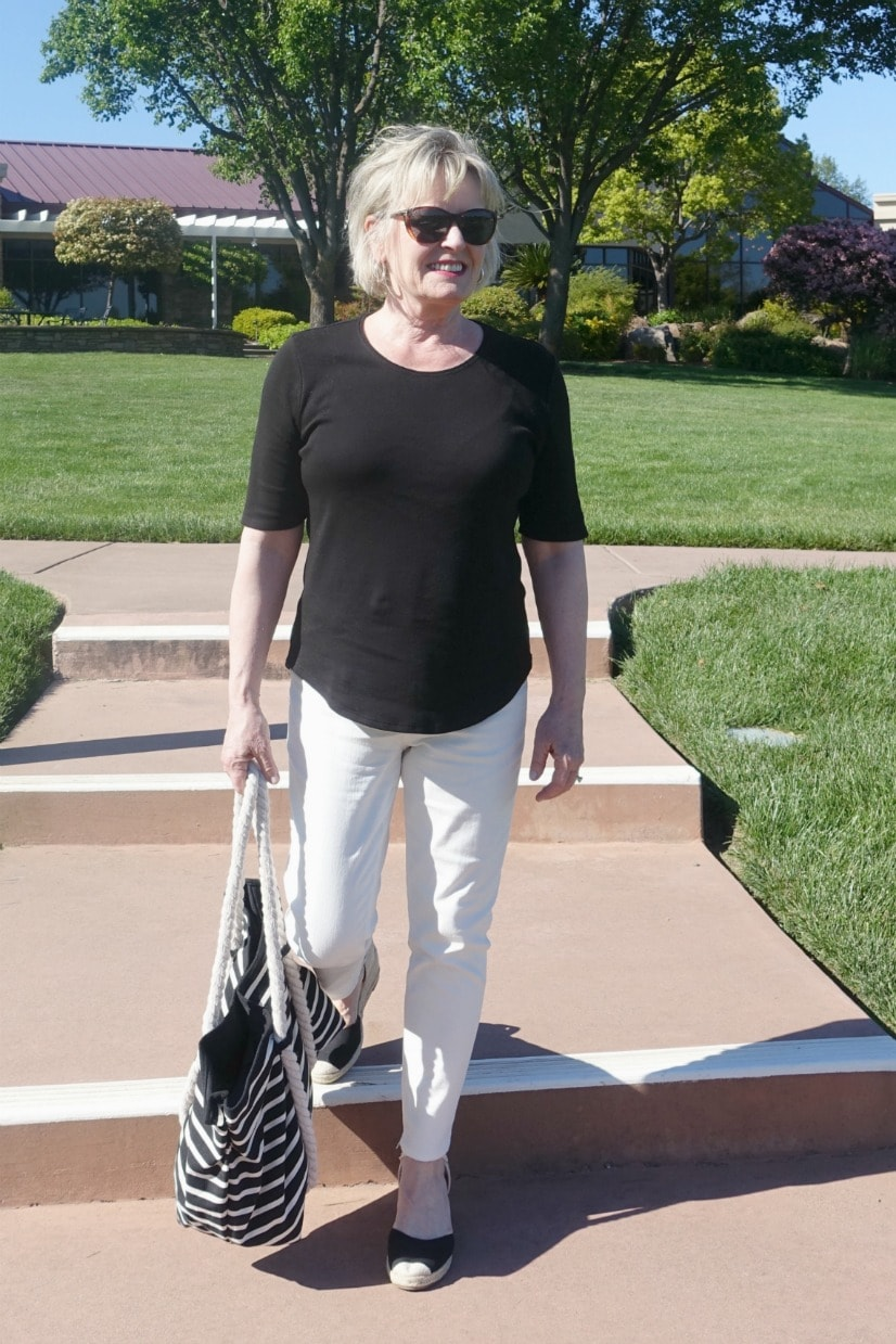 Jennifer from A Well Styled Life wearing black and cream colored outfit with striped tote and espadrilles