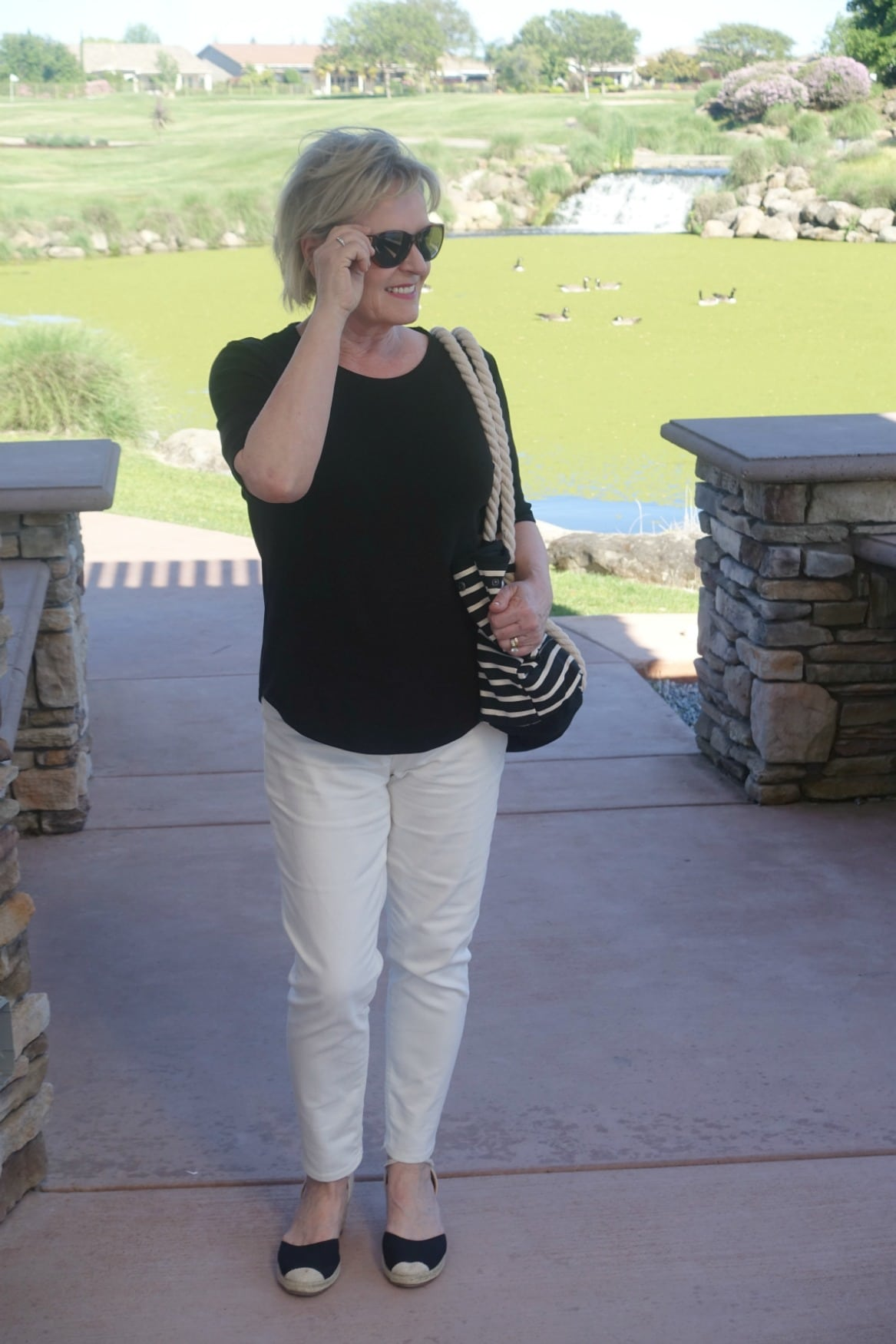 Jennifer of A Well Styled Life wearing black tee, cream colored jeans, black espadrilles and black striped tote