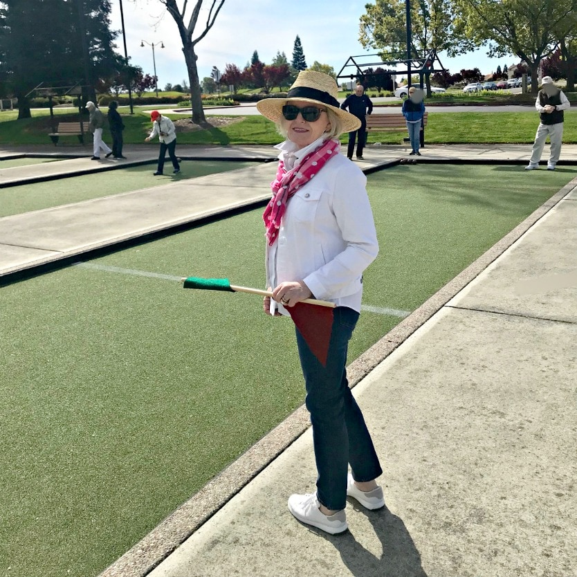 Jennifer Connolly of A Well Styled Life wearing casual outfit of white denim jacket, black jeans, white tennis shoes, pink scarf and straw hat