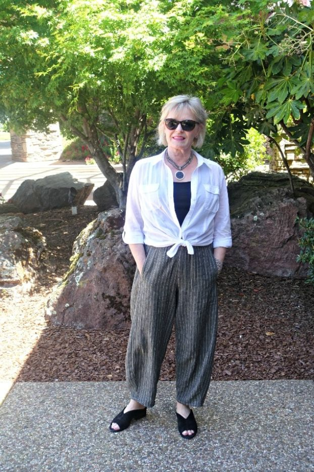 Jennifer of A Well Styled Life wearing white shirt tied at waist, taupe lantern pant and black sandals