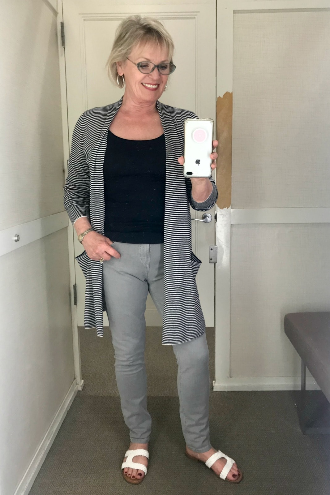 Jennifer of A Well Styled Life wearing a striped cardigan, gray skinny crop jeans from Loft