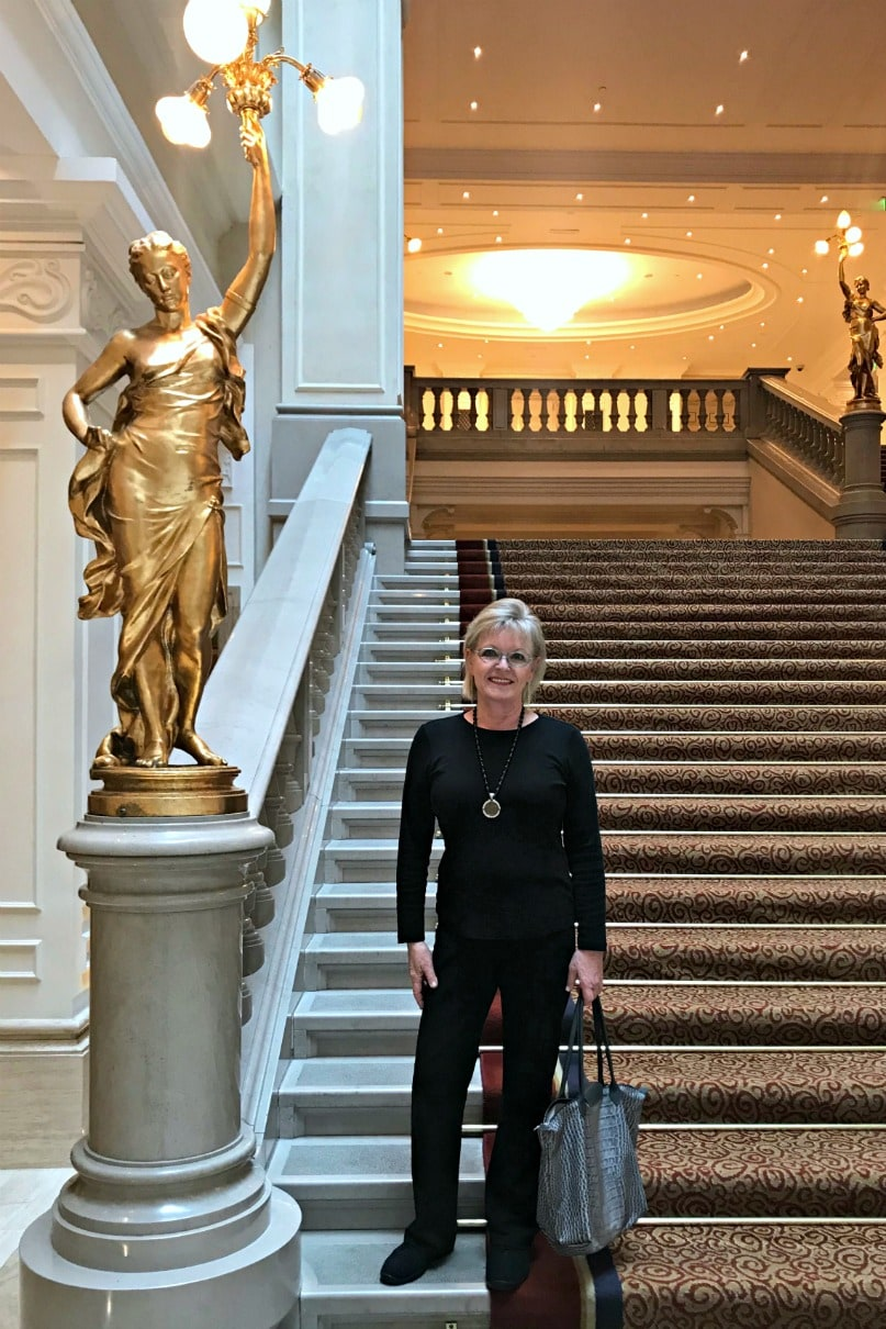 Jennifer Connolly of A Well Styled Life wearing black on the grand staircase of the Corinthia Hotel in Bucharest