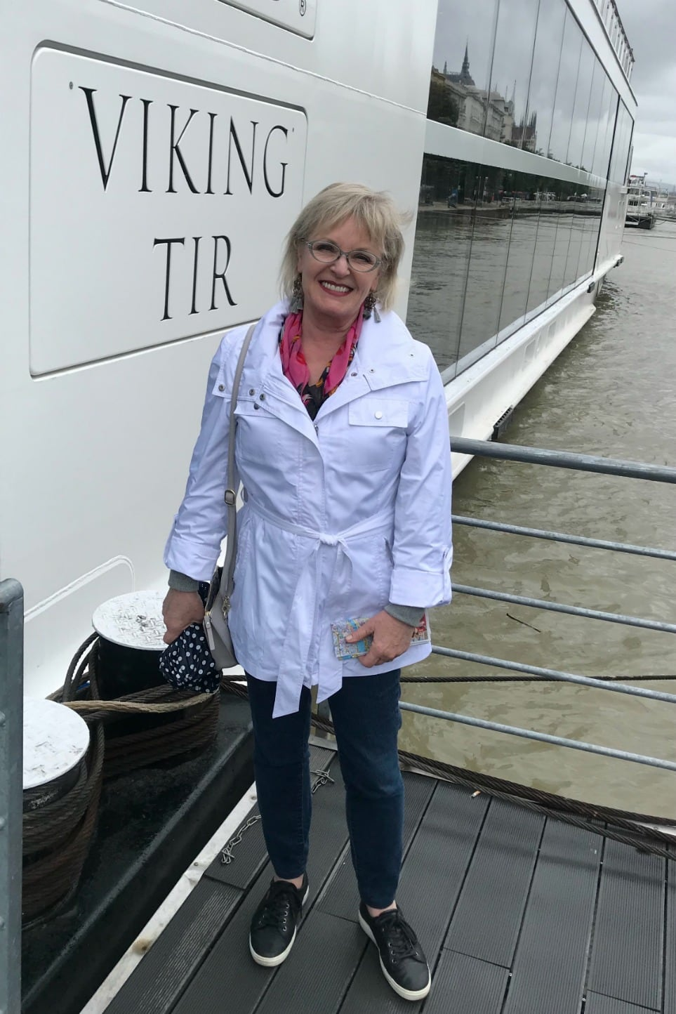 Jennifer Connolly of A Well Styled Life wearing white jacket and blue jeans boarding a Viking ship in Bucharest