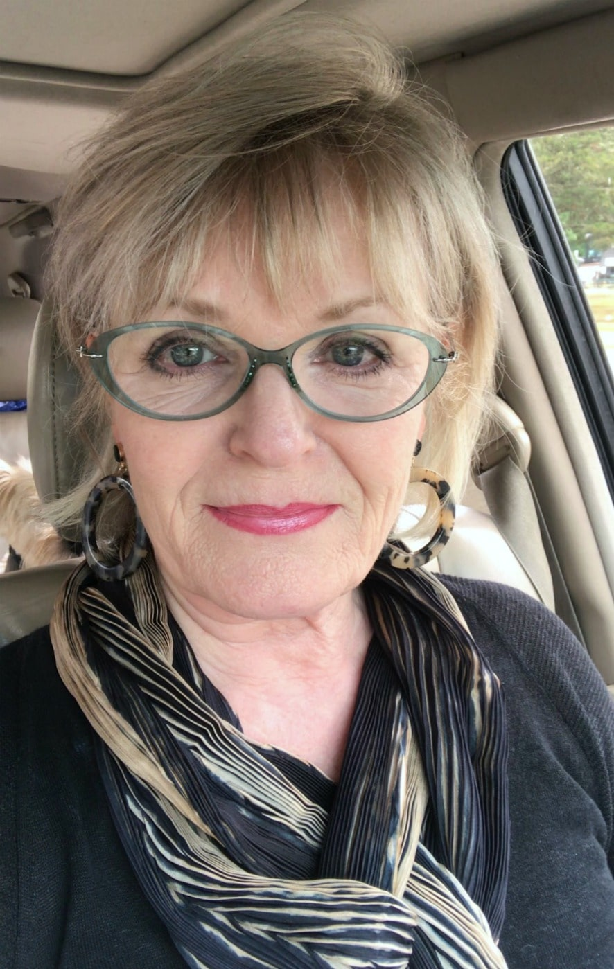 Jennifer Connolly of A Well Styled Life traveling in and RV we with beige and black scarf and Target earrings