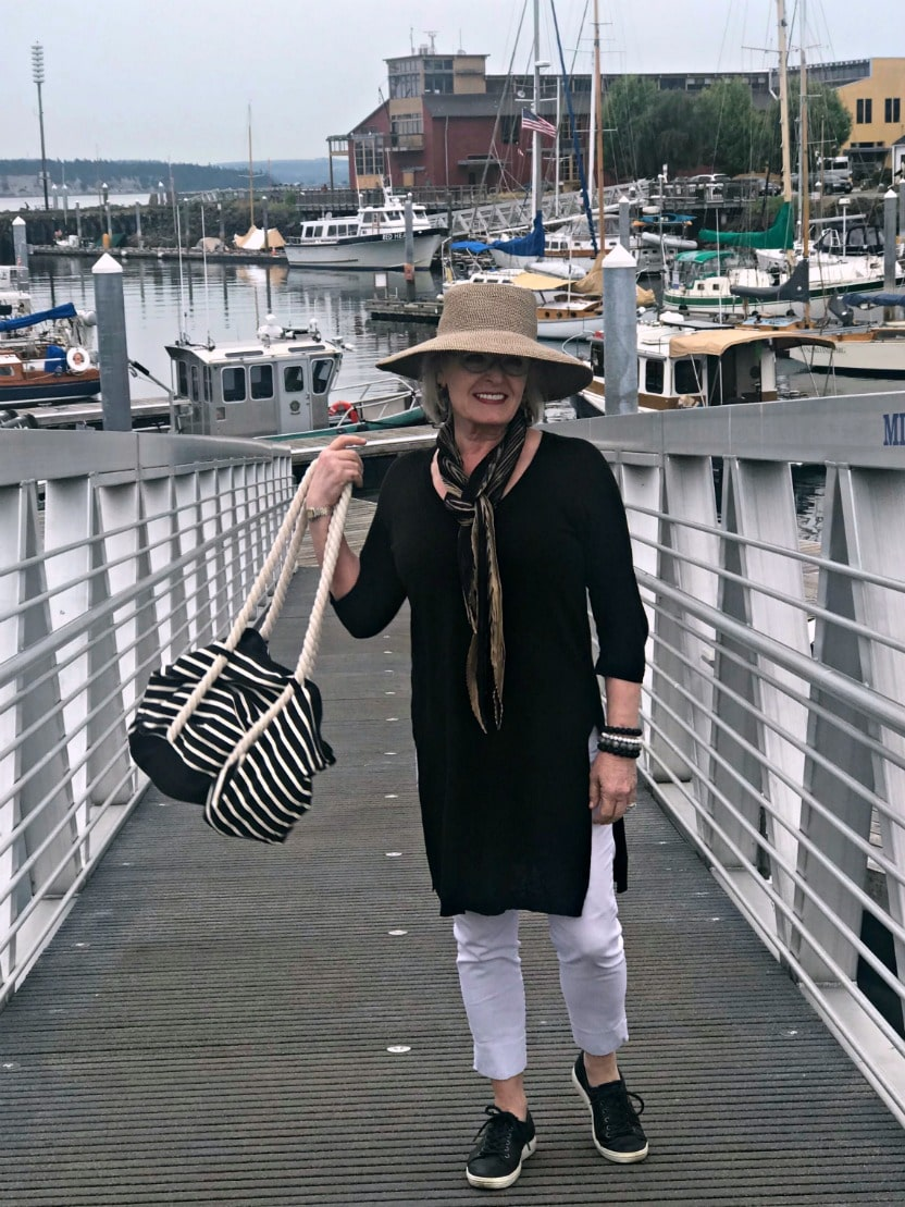 Jennifer Connolly of A Well Styled Life wearing long black tunic over white stretch pants with beige hat and black sneakers on the dock at Port Townsend, WA