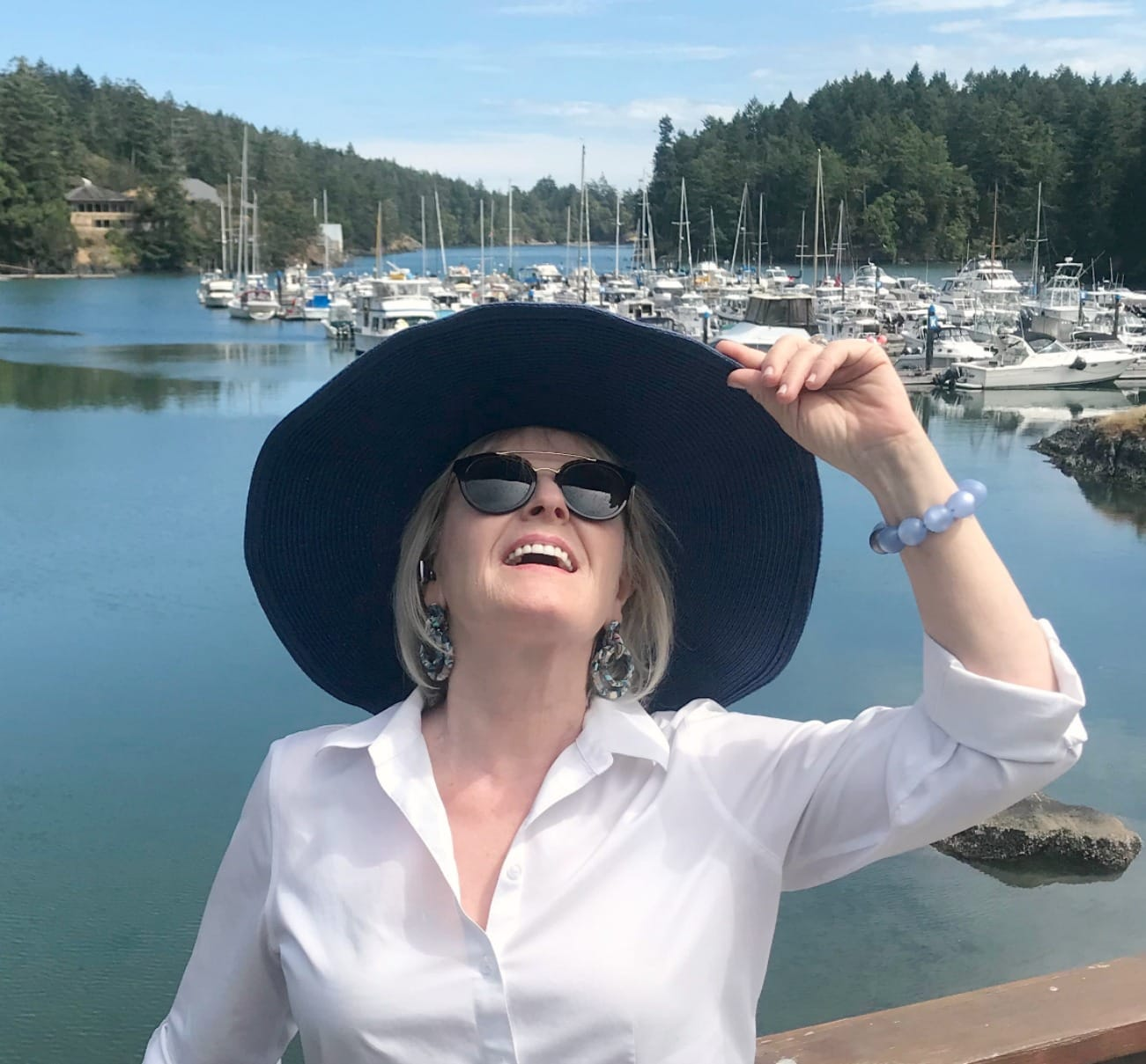 Jennifer Connolly of A Well Styled Life wearing large blue hat and white shirt at a marina