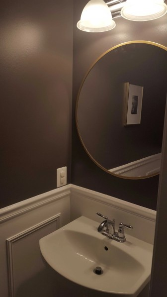 Powder Room Wall with Brass Circular Mirror