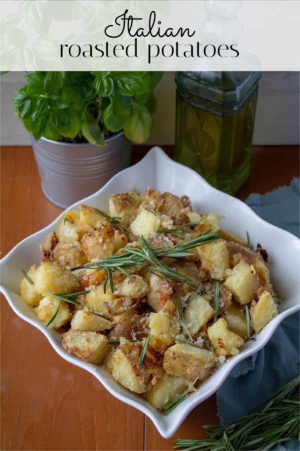 Italian Roasted Potatoes in a white bowl with basil and olive oil in the background
