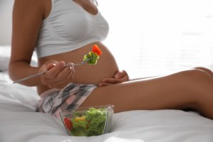 Young pregnant woman with bowl of vegetable salad on a bed