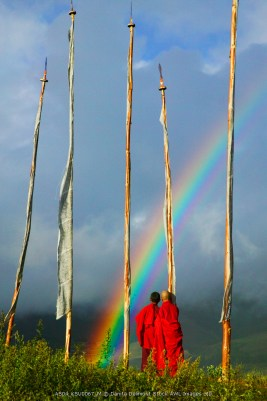 Bhutan, Gangtey village, Rainbow over two monks with praying flags in the Phobjikha Valley (MR)