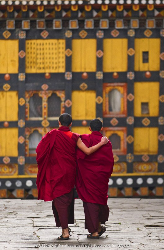 Asia, Paro Dzong, Paro, Bhutan. Young monks enjoying a moment of relaxation and companionship in the courtyard of their Dzong between prayer sessions and classes.