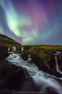 Grundafjordur, Snaefellsness peninsula, Western Iceland. Northern lights above the Kirkjufellfoss waterfall and Kirkjufellsa river.