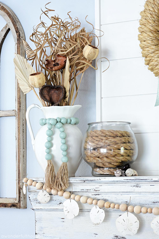 Pichet blanc avec des perles de sarcelle au-dessus d'une guirlande côtière de perles de bois