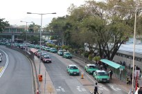 Red urban taxis and green New Territories cabs are waiting for passengers at a taxi stand in the Sha Tin district.