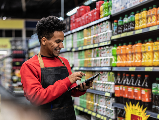 Male grocery employee smiling and using mobile device in front of product shelves.