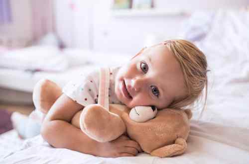 Cute little girl with her teddy bear at home lying on bed in bedroom