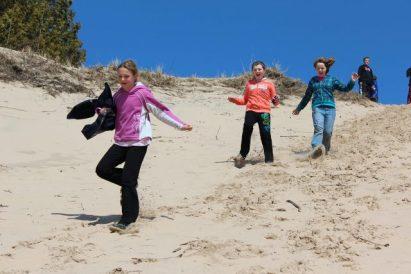 Children run down sand dune at Miniwanca