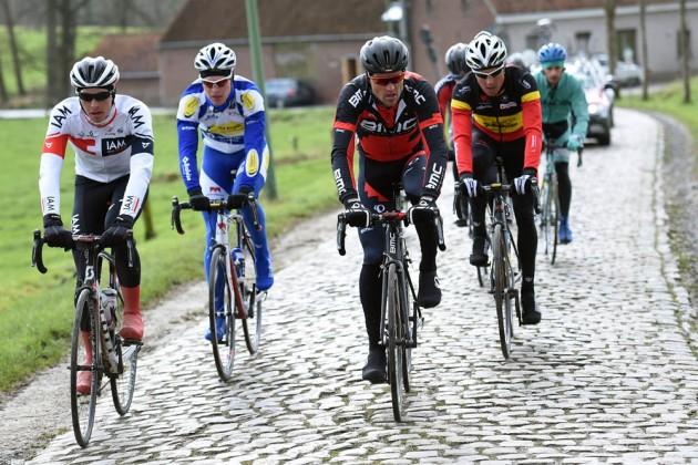Bir anıtsal klasik olmasa da Omloop Het Nieuwsblad ile bahar klasikleri Belçikadan başlıyor. Yarış Gent kentinden başlayıp 200 km boyunca dolana dolana yeniden Gent kentine sona eriyor; yarışın 60 km'si ise kaldırım (cobble, pave) taşı ve gent denilen anlık sert, hatta ikisi bir arada saçma sapan ve taşlı; tırmanışlardan oluşuyor. Fotoğrafta yarış öncesi takımların bir arada literatürde recon ride denilen idman sürüşü yaptıklarına tanıklık ediyoruz. İdman sürüşlerinde tercih edilecek lastiklerin çapından basıncına, kullanılacak vites oranlarına, nerede kim atak yapacak sorusuna dek cevaplar aranıyor. Şimdi bir aradalar, ancak yarış günü hepsi hem zorlu yollar ve soğuk havayla, hem de birbirileriyle mücadele edip zafere pedallamaya çalışacaklar.