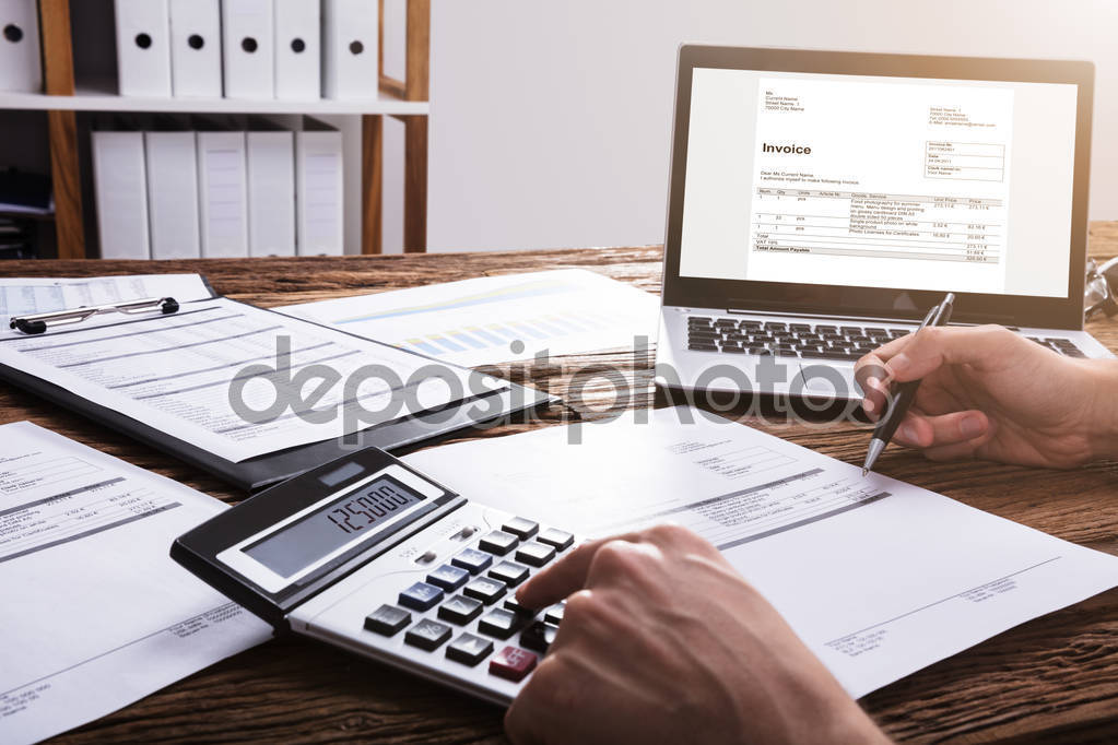 Close-up Of A Businessperson's Hand Calculating Bill With Laptop On Wooden Desk