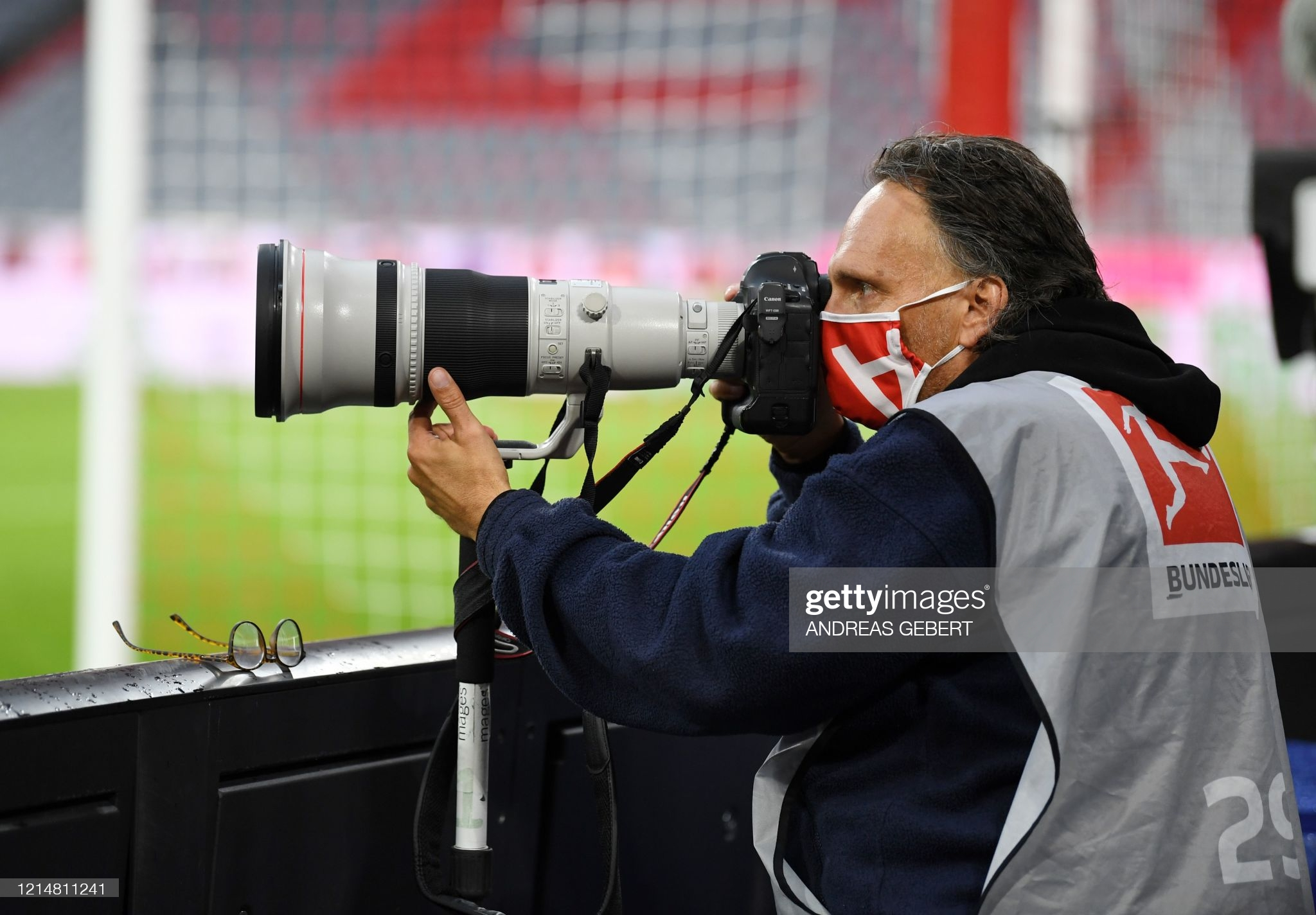 A photographer wears a protective face mask during the German first division Bundesliga football match between FC Bayern Munich and Eintracht Frankfurt on May 23, 2020 in Munich, southern Germany. (Photo by ANDREAS GEBERT / POOL / AFP) / DFL REGULATIONS PROHIBIT ANY USE OF PHOTOGRAPHS AS IMAGE SEQUENCES AND/OR QUASI-VIDEO (Photo by ANDREAS GEBERT/POOL/AFP via Getty Images)