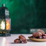 Dates close-up in the foreground. On the distant plan a slightly blurry Burning, lighting, glowing Ramadan Lantern on a white table, textured dark green wall background. Place for text on the right