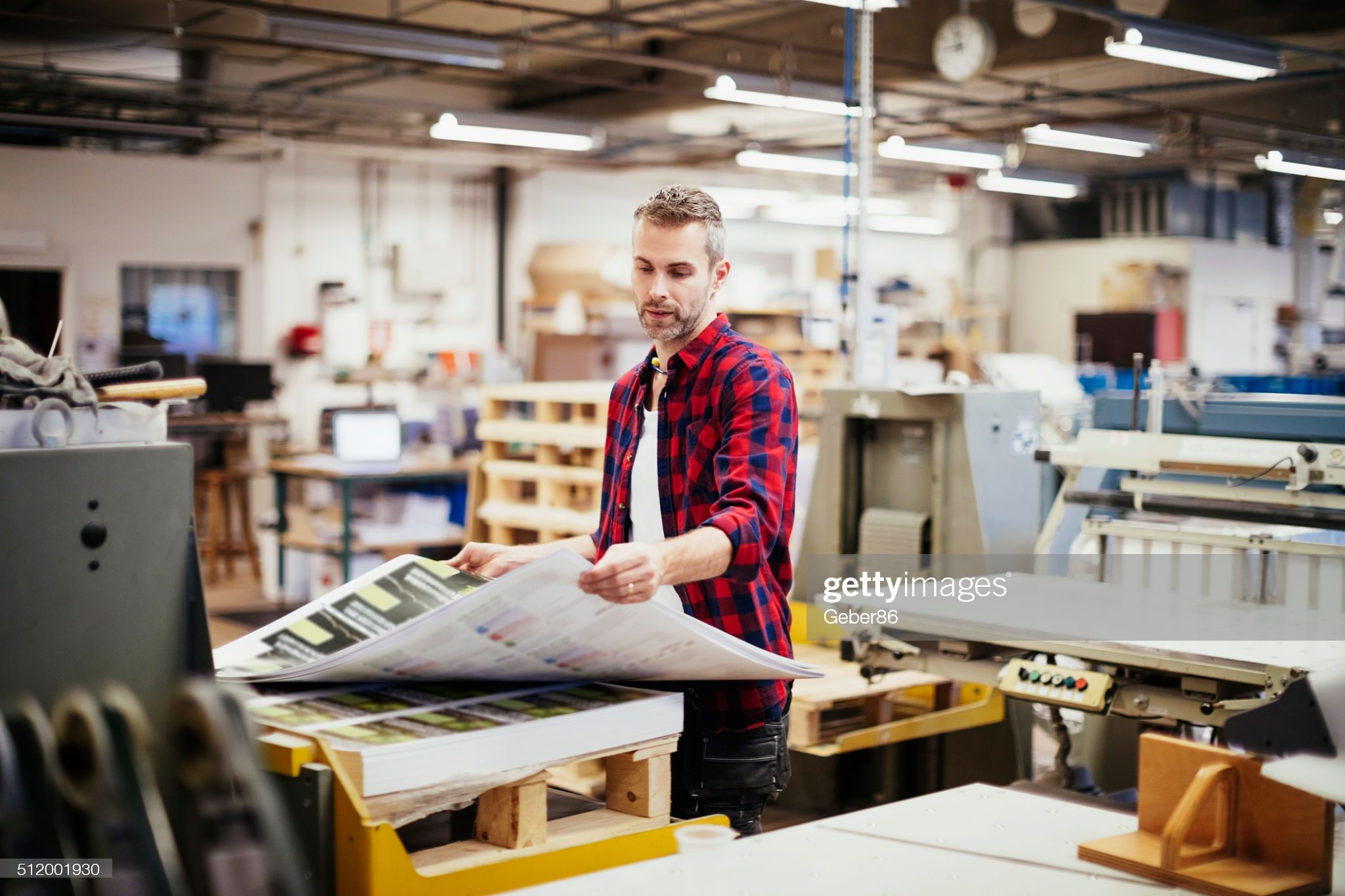 Photo of a man working  in printing factory