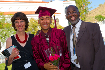 Ombudsman student in cap and gown smiling with parents