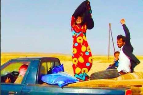 كردية ترفع عباءتها احتفالا لحظة عبورها الحدود واقترابها من سيطرة كردية
