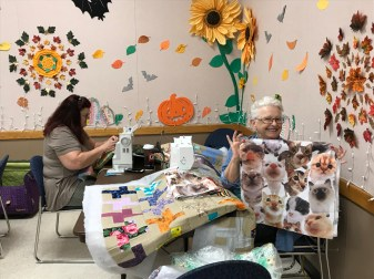 Mary B (left) is busy sewing, while Allie W (right) shows cute kitty fabric.