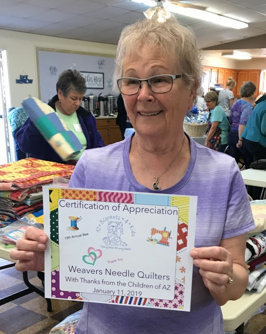 Sharon L shows a Certificate of Appreciation for our 12th Annual Bee at Weavers Needle.