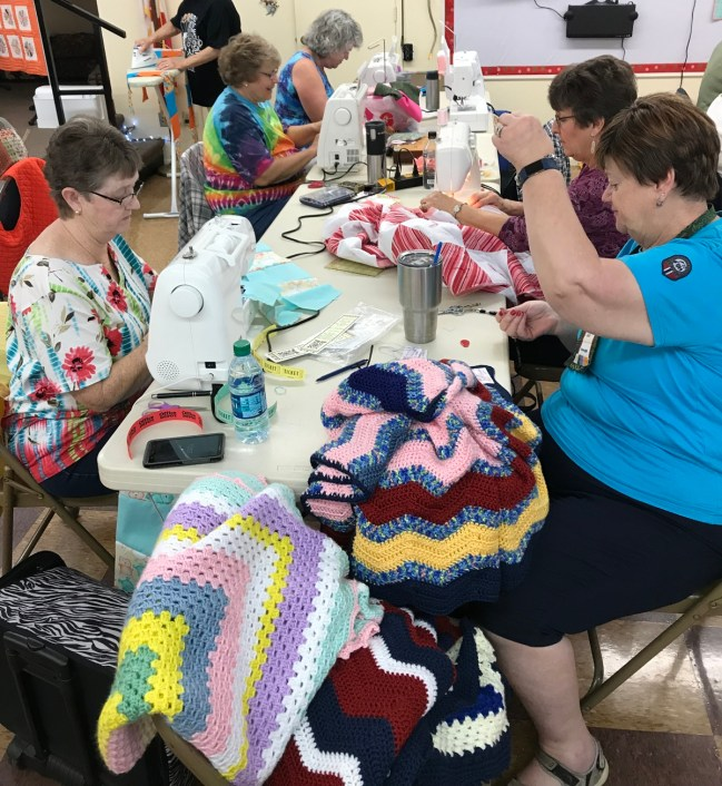 Busy sewing machines and a volunteer who kindly added our labels to knit and crochet blankets.