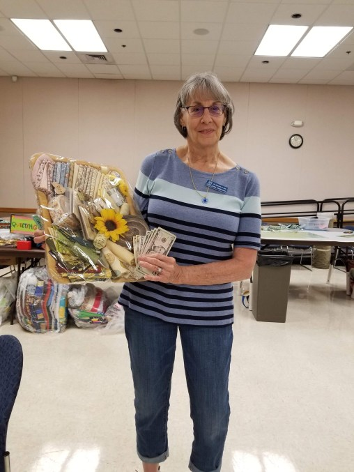 Linda wins the 50/50 and the fabric raffle basket! She won the 50/50 here last year too! Lucky!
