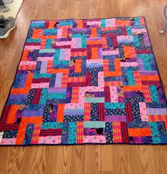 Colorful quilt made with a few fat quarters, sewn into strip sets, cut, and rotated.