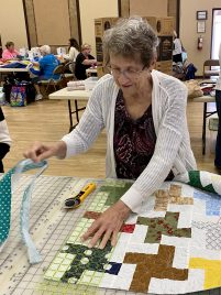 Margaret trims the quilted or tied blankets before sending them on to our binding team.