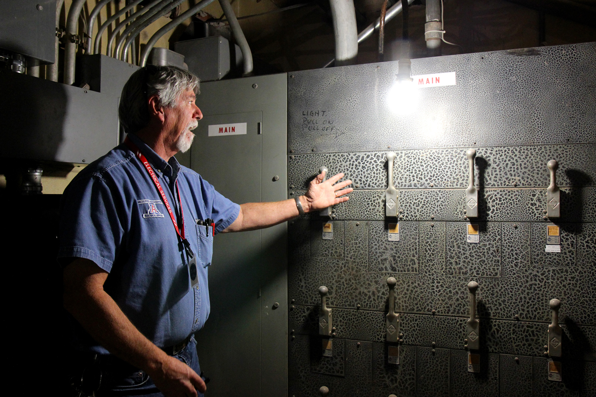 """University of Arizona Facilities Management Electrician Joe Thomasson explains the pattern on the electrical panel underneath the Arizona State Museum is known as """"alligator"""" paint on Wednesday, May 17, 2017. The electrical panel is an original system from when the museum was built in 1924. (Photograph by Julianne Stanford/AZCIR)"""
